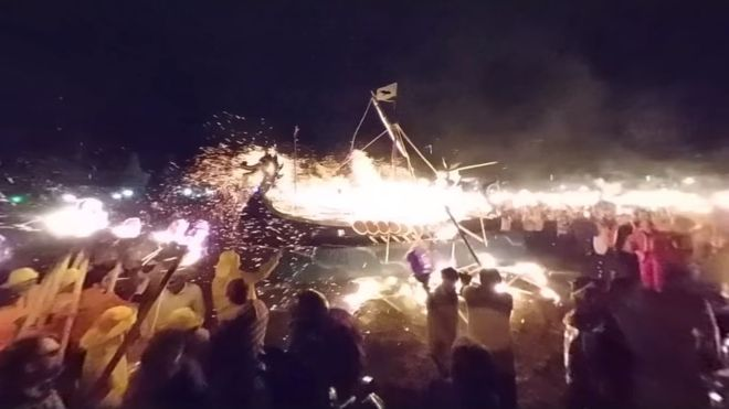 viking boat on fire at a ceremony on shetland isles