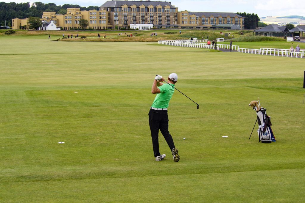 Man in a green shirt playing golf at St Andrews Golf Course Scotland
