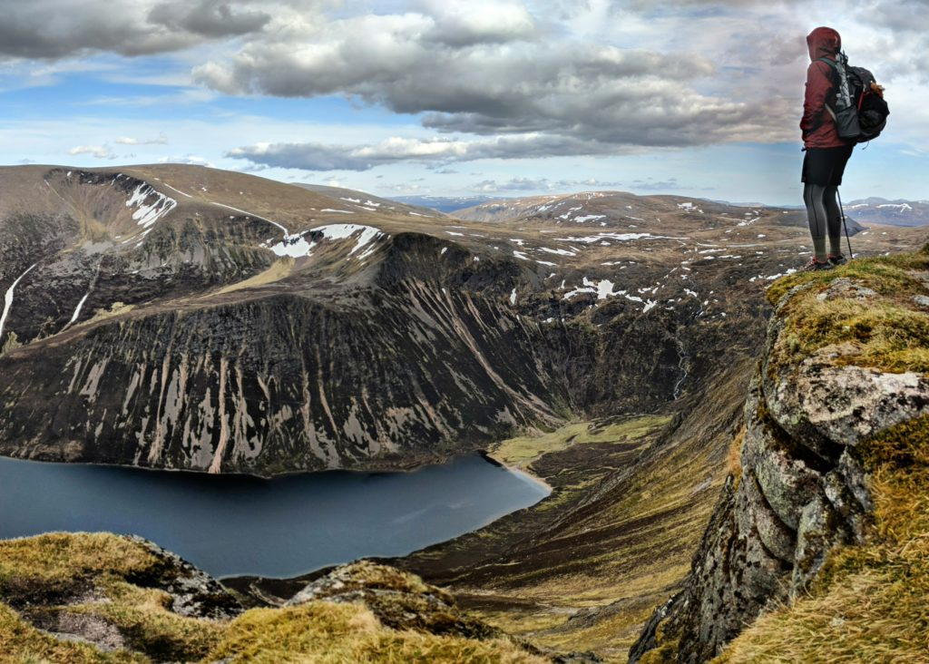 man on top of a mountain above a loch in scotland