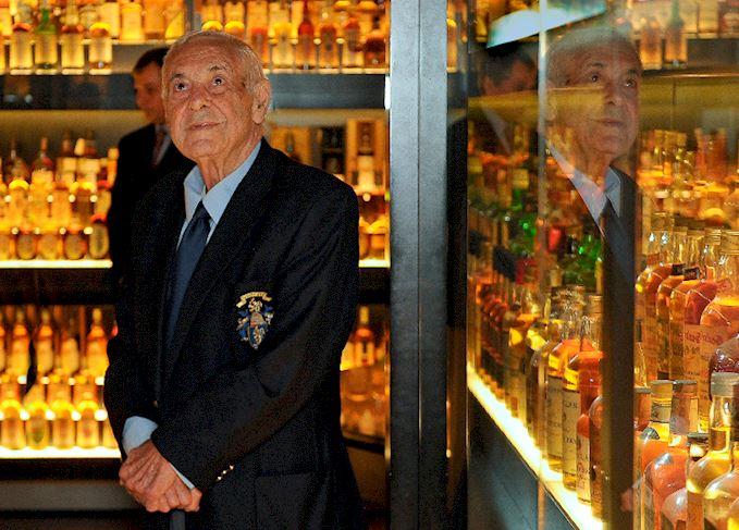 man looking at whisky bottles