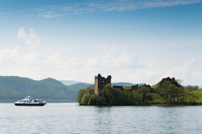 Cruise boat beside Urquhart Castle on Loch Ness