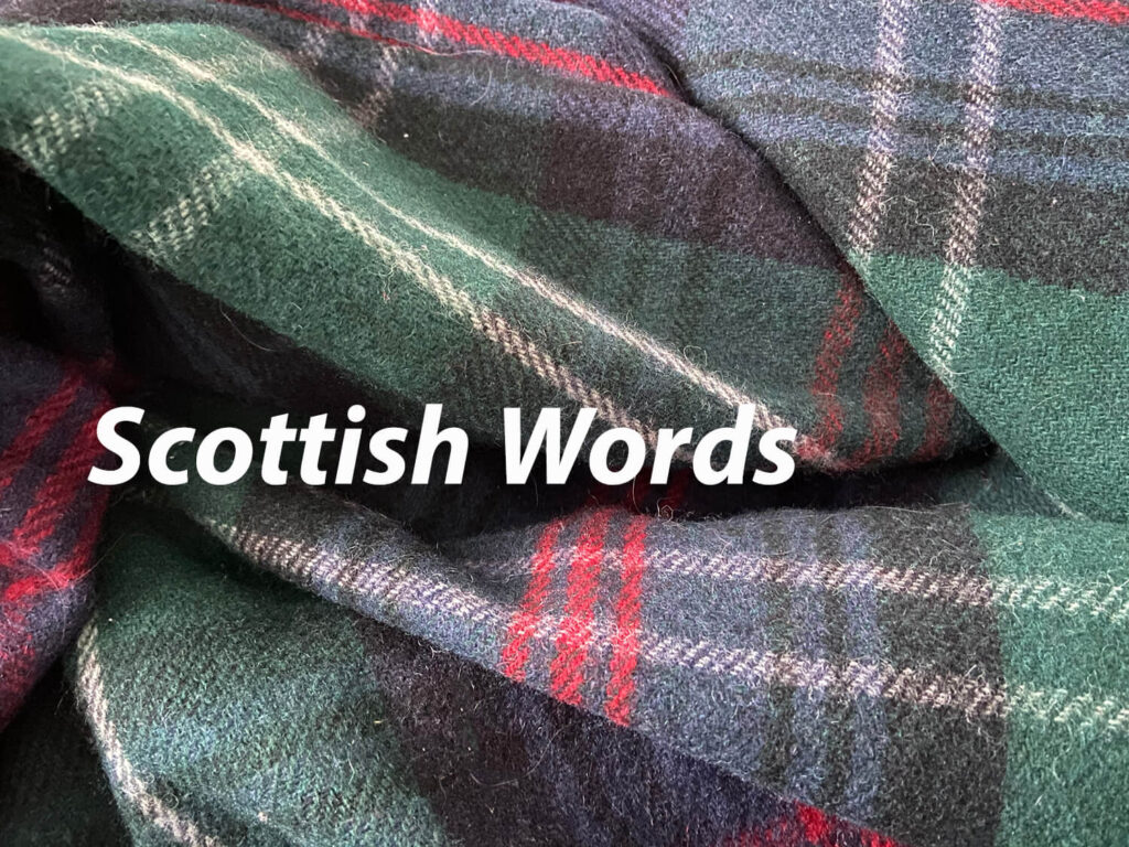 a tartan blanket with Scottish words written across the top